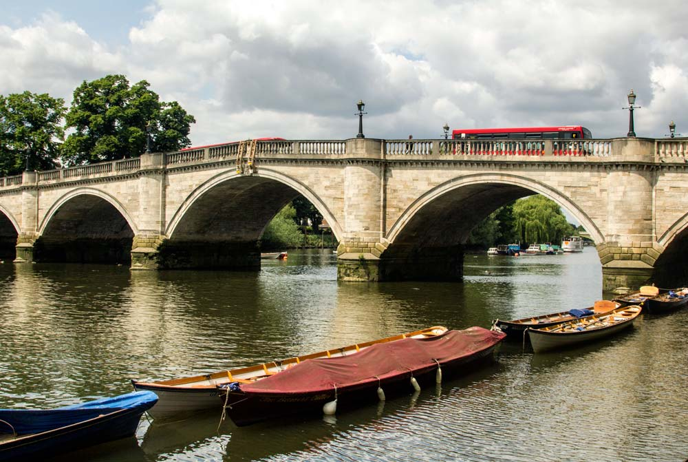 rowboats moored at side of river with bridge in background