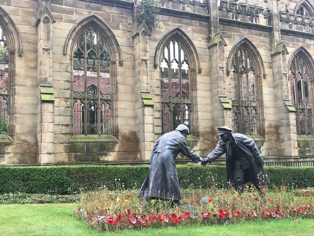 statue of two soldiers shaking hands in front of bombed out church
