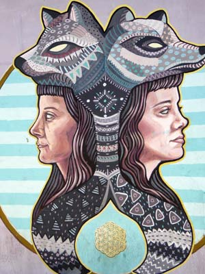 wall mural of two women with wolves heads and serpents backs