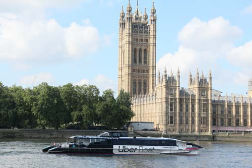 black and white thames river boat passing the gothic houses of parliament building