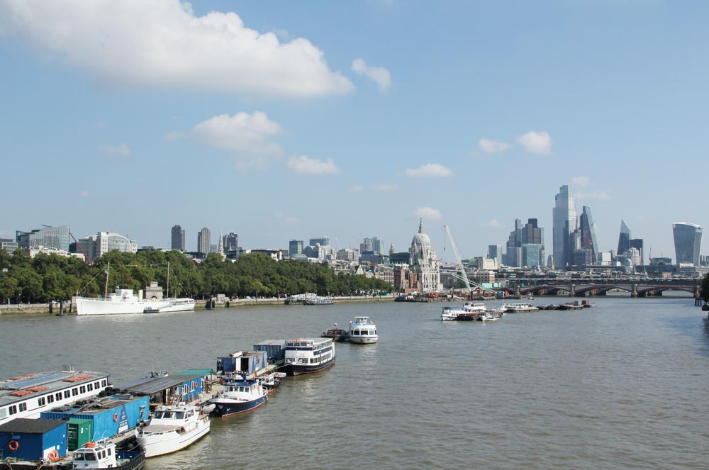 view of river thames with small boats and skyscrapers in distance