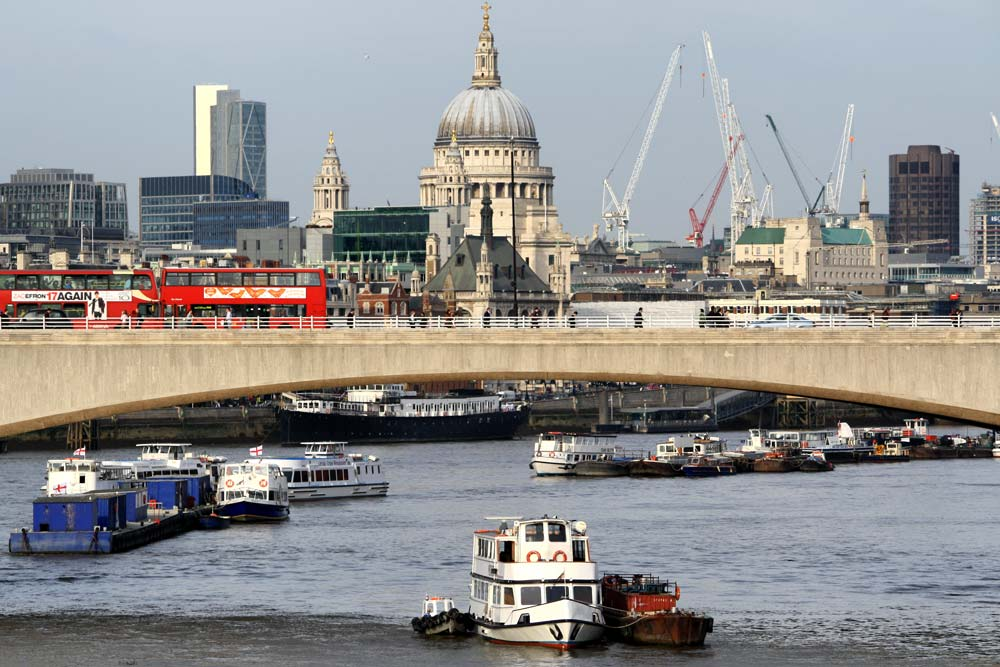 concrete bridge over river thames in london with red buses and cathedral dome in background