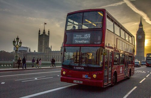 double decker bus on bridge at sunset