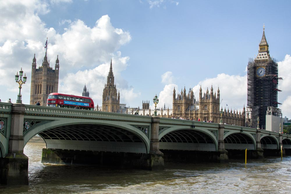 red bus crossing bridge over the thames in london with houses of parliament and big ben