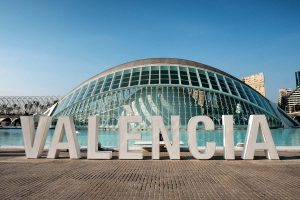sign spelling valencia in front of lake and futuristic dome-shaped building